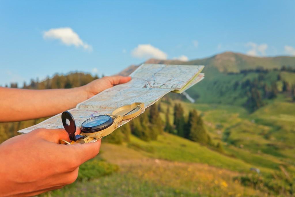 turysta trzyma w ręce kompas i mapę